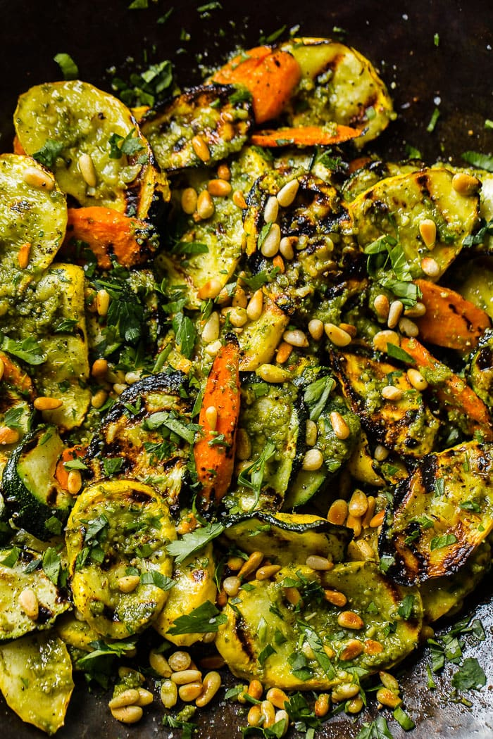 A close up of grilled veggies with pesto, parsley and toasted pine nuts including zucchini, yellow squash and carrots for a 15 minute grilled veggies with pesto recipe