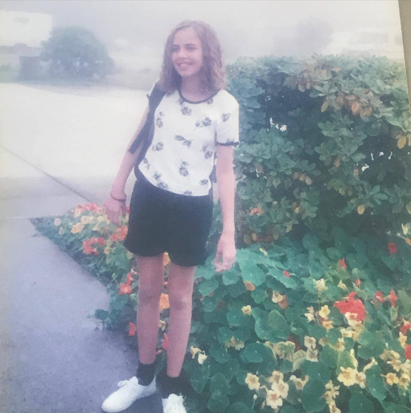 a photo of a junior high school girl with a backpack strap over one shoulder
