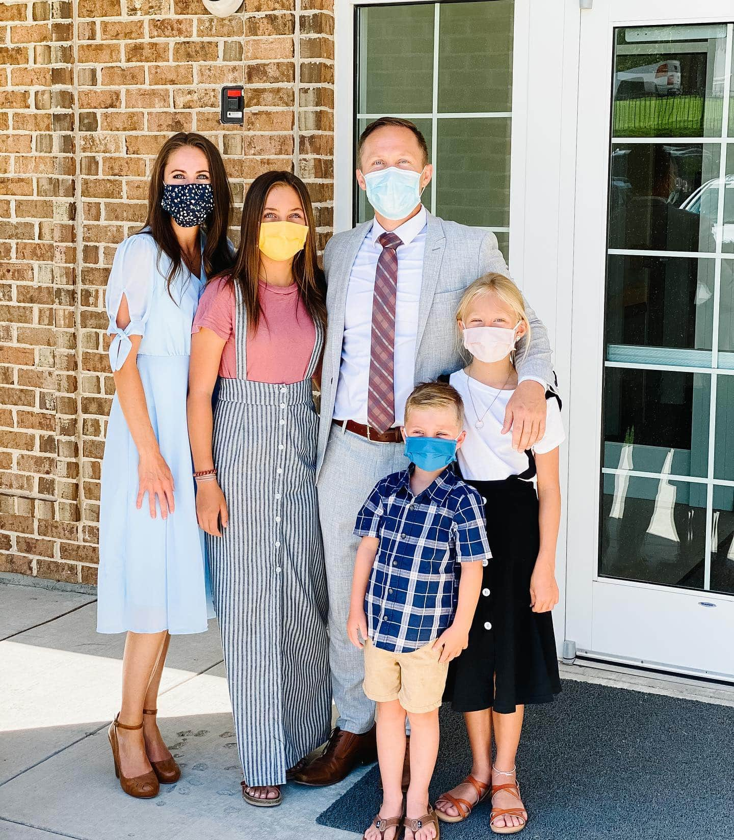 A photo of a family all wearing masks outside of a church building.