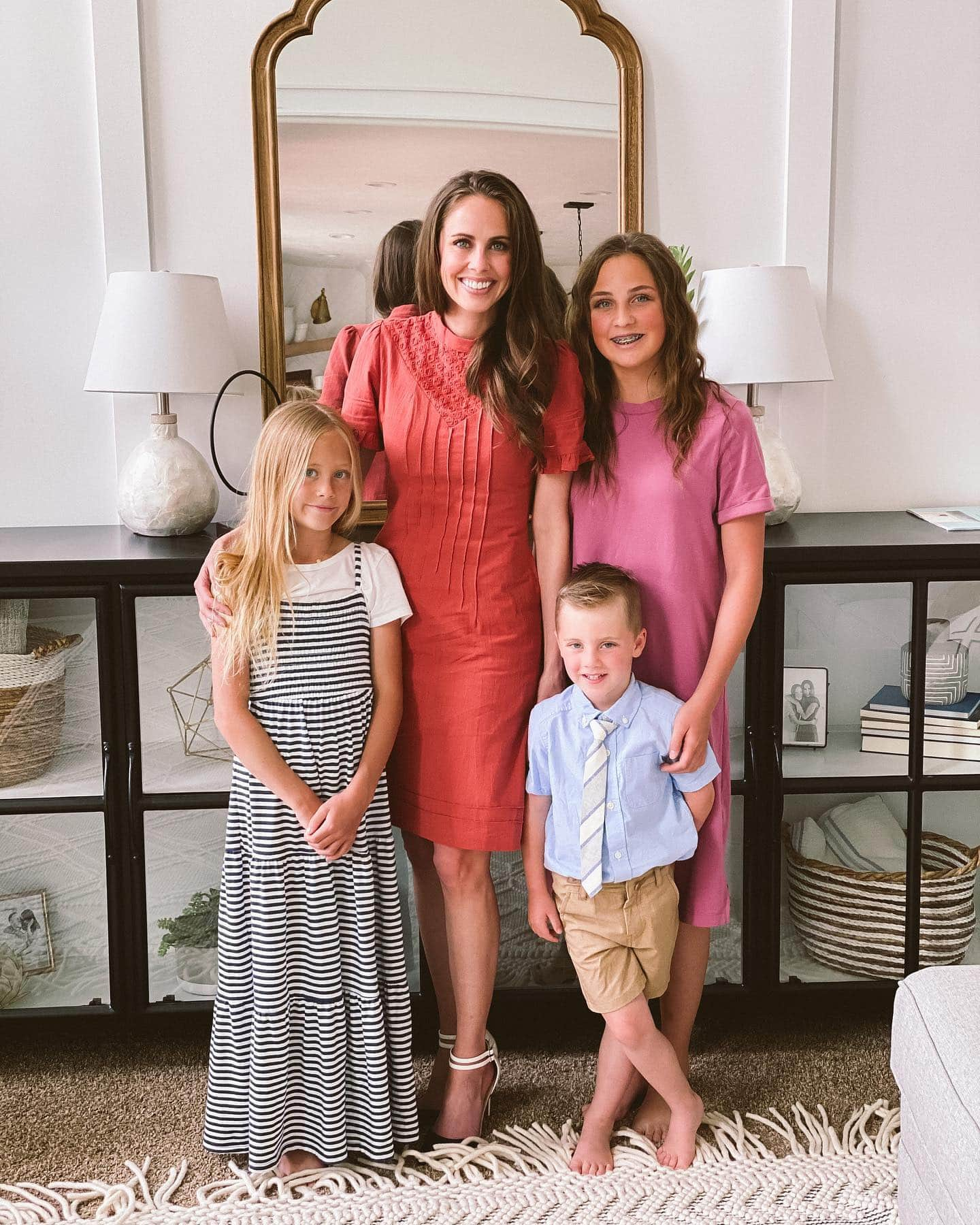 A photo of a mom with her three kids all in Sunday dress.