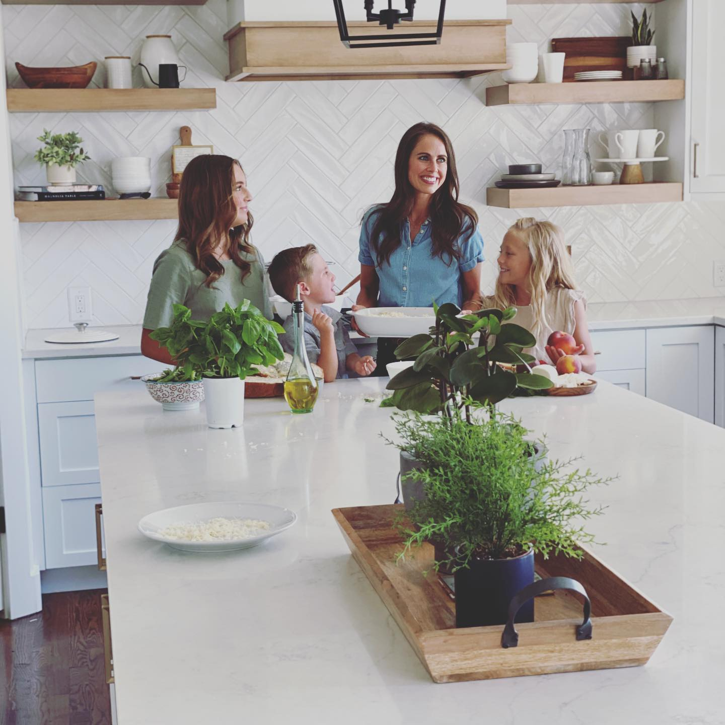 A photo of a mom in the kitchen with her three kids.
