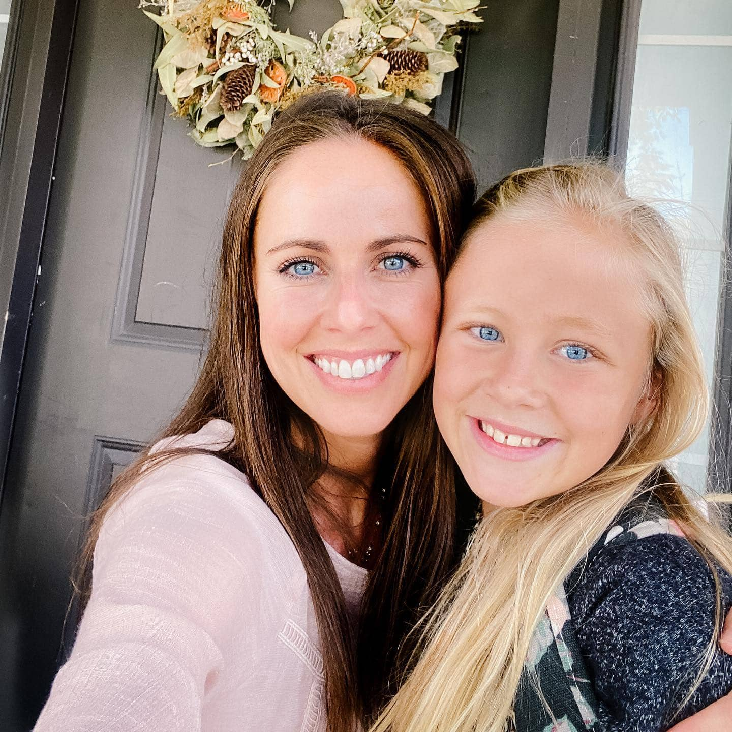 A selfie of a mother and daughter standing outside the front door.