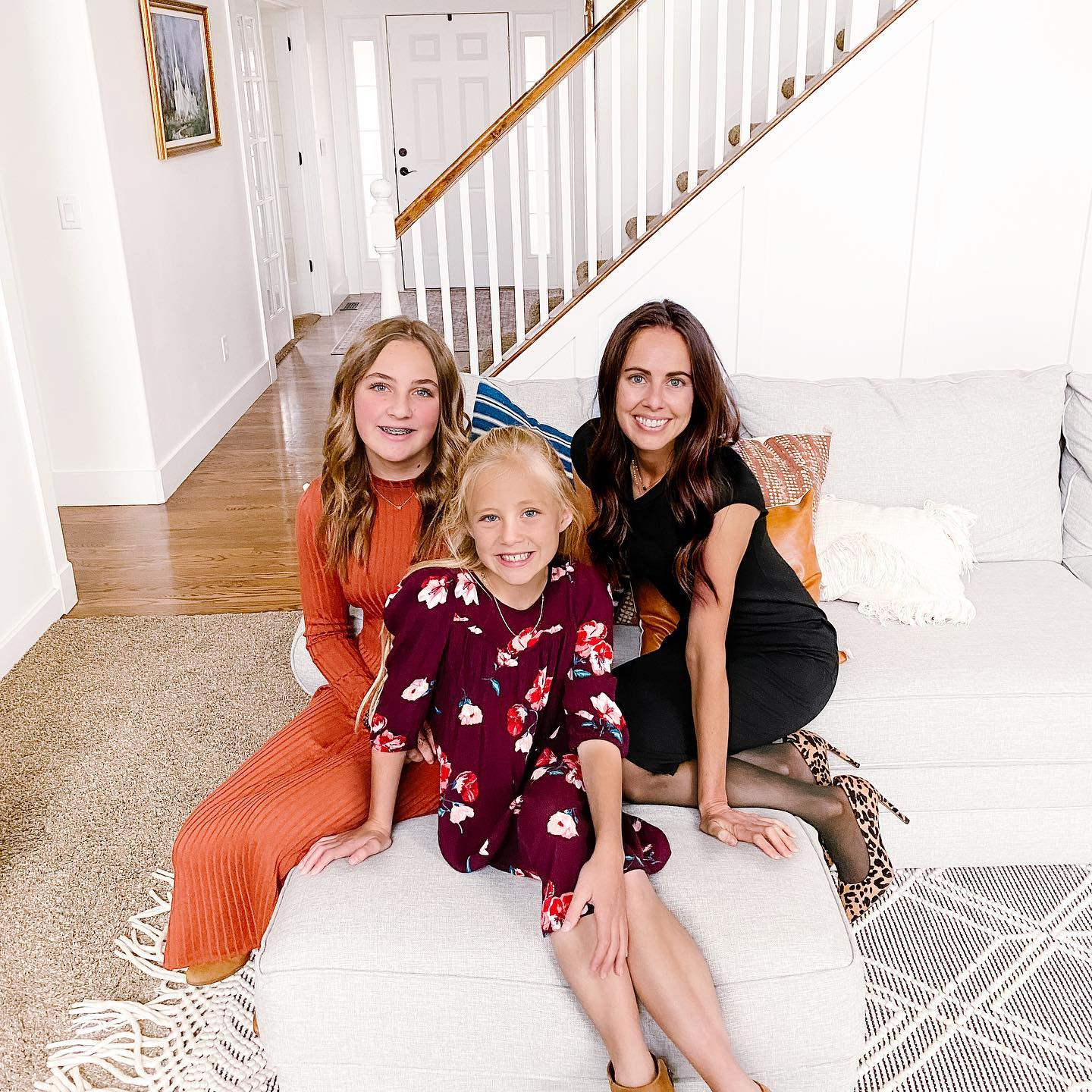 A photo of a mother with no makeup on sitting next to her daughters on a couch.