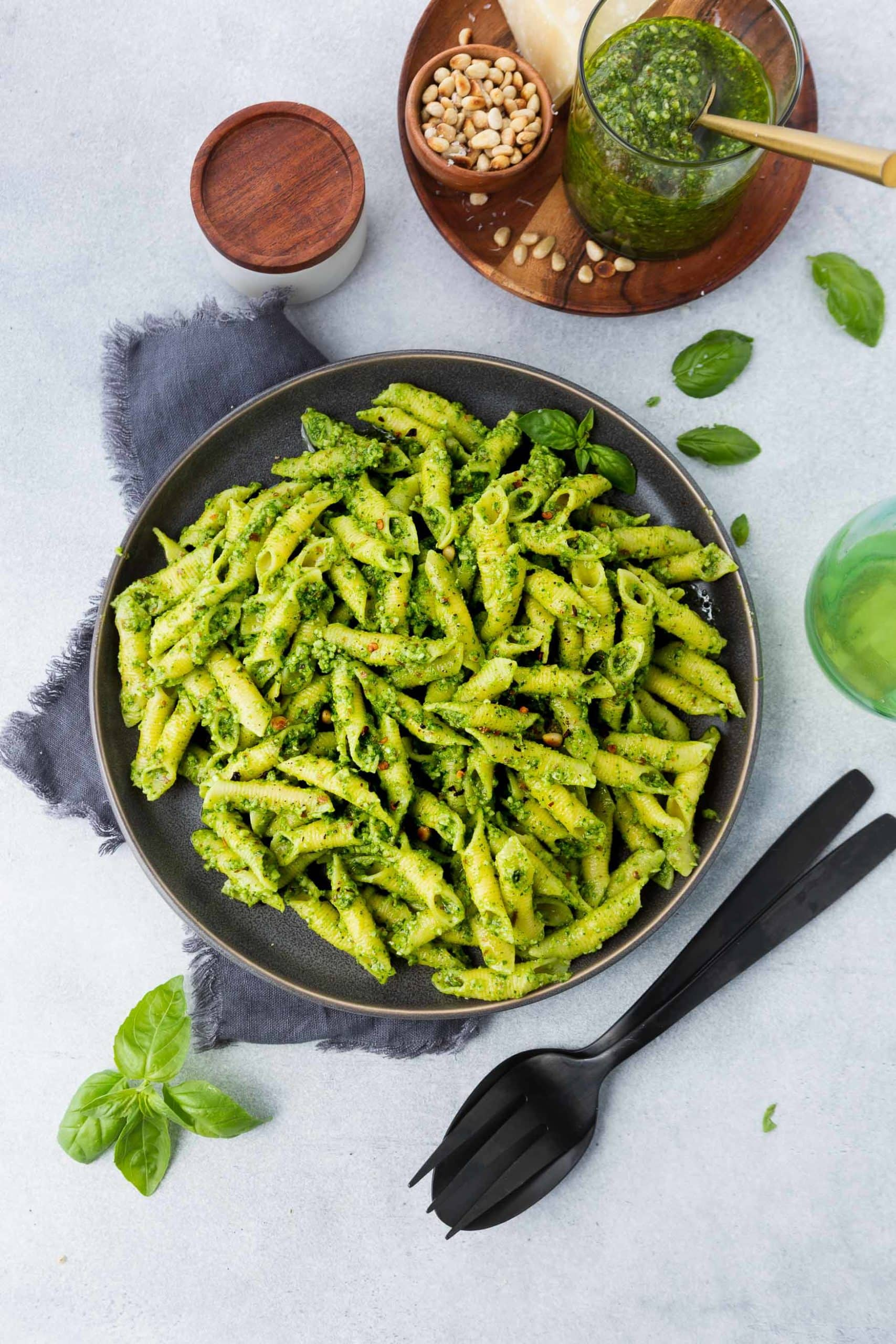 a photo of a plate of cooked penne pasta covered in bright green pesto with a cup of fresh pesto next to it and a jar of pine nuts on the side