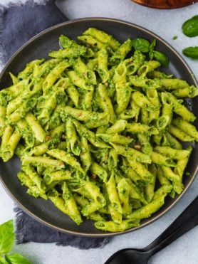 a close up photo of a plate full of bright green pesto covered penne pasta.