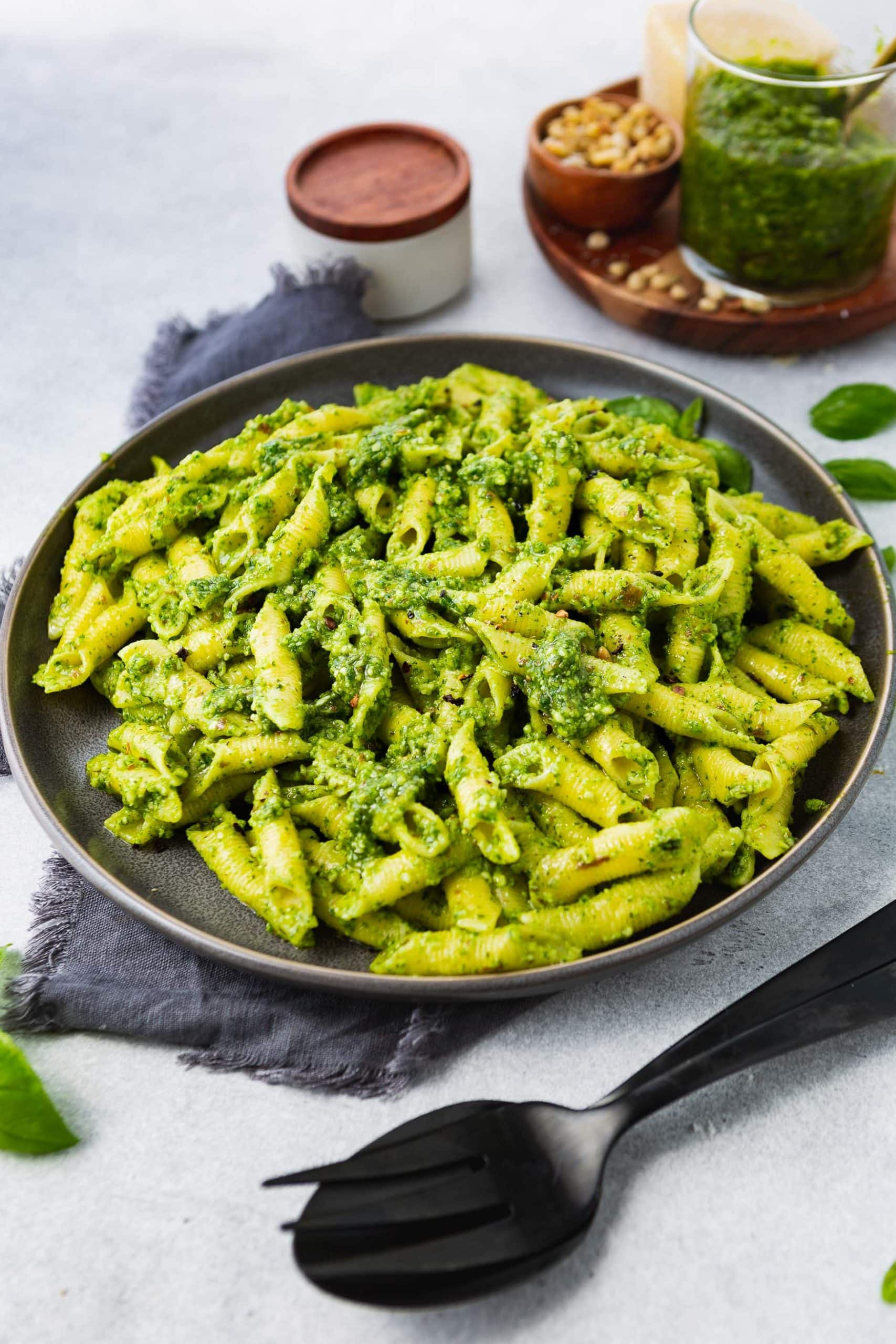 a photo of a charcoal gray plate full of penne pasta covered in homemade pesto