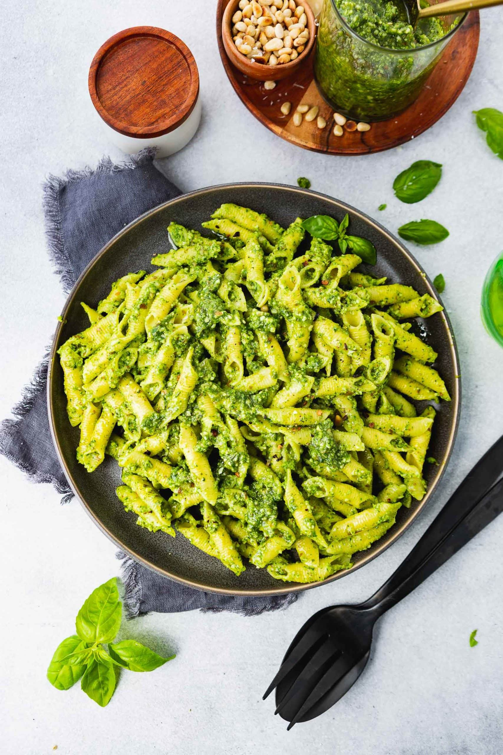 a photo of a plate of bright green pesto penne pasta with a fork and spoon sitting next to the plate and fresh basil leaves scattered around the plate.