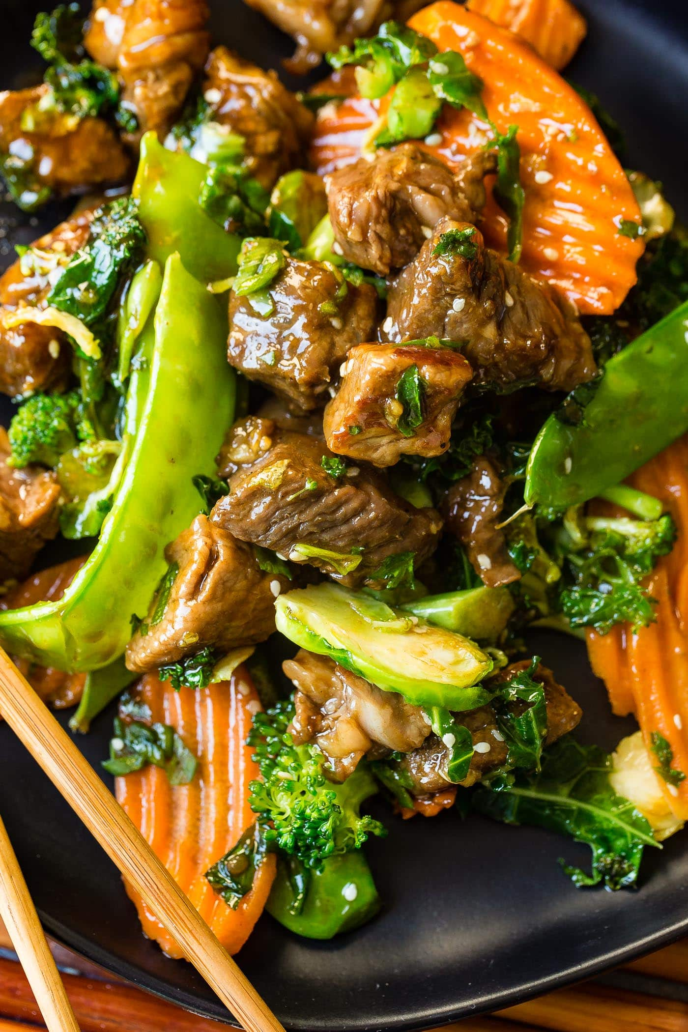 A close up photo of sesame steak stir fry loaded with vegetables.