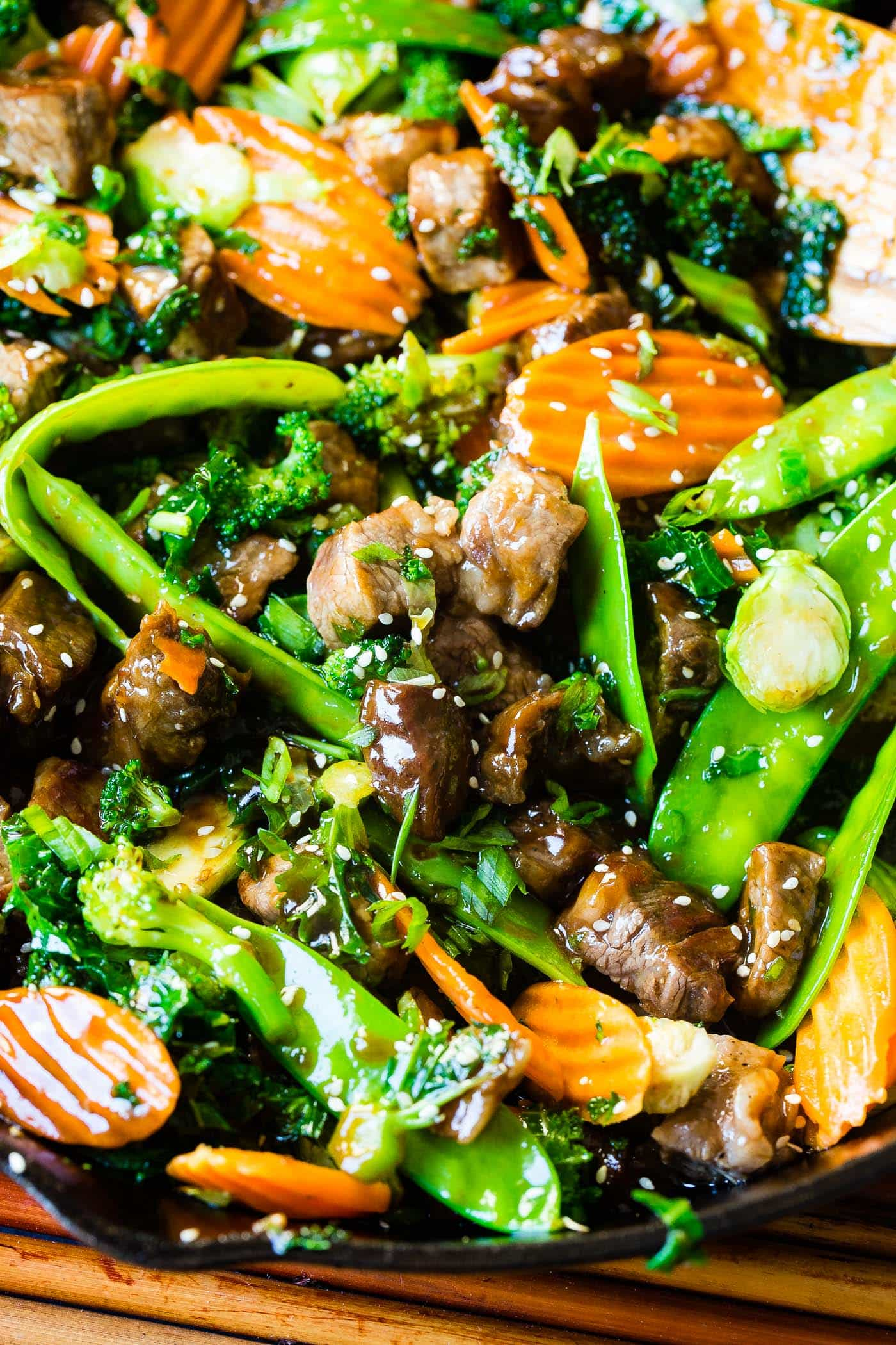 A photo of sesame steak stir fry loaded with vegetables and topped with sesame seeds.