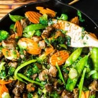 A cast iron skillet full of sesame steak stir fry with a wooden spoon ready to serve.