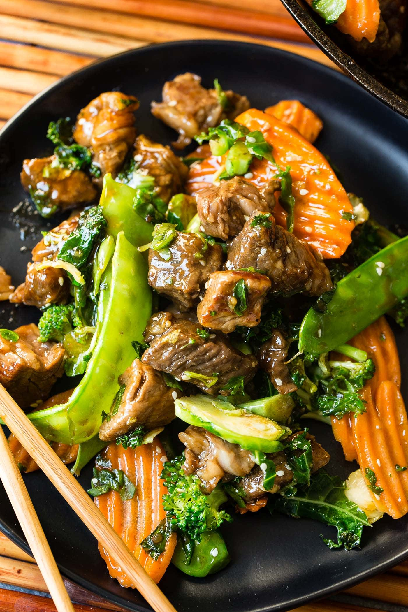 A close up photo of sesame steak stir fry loaded with vegetables with chopsticks.