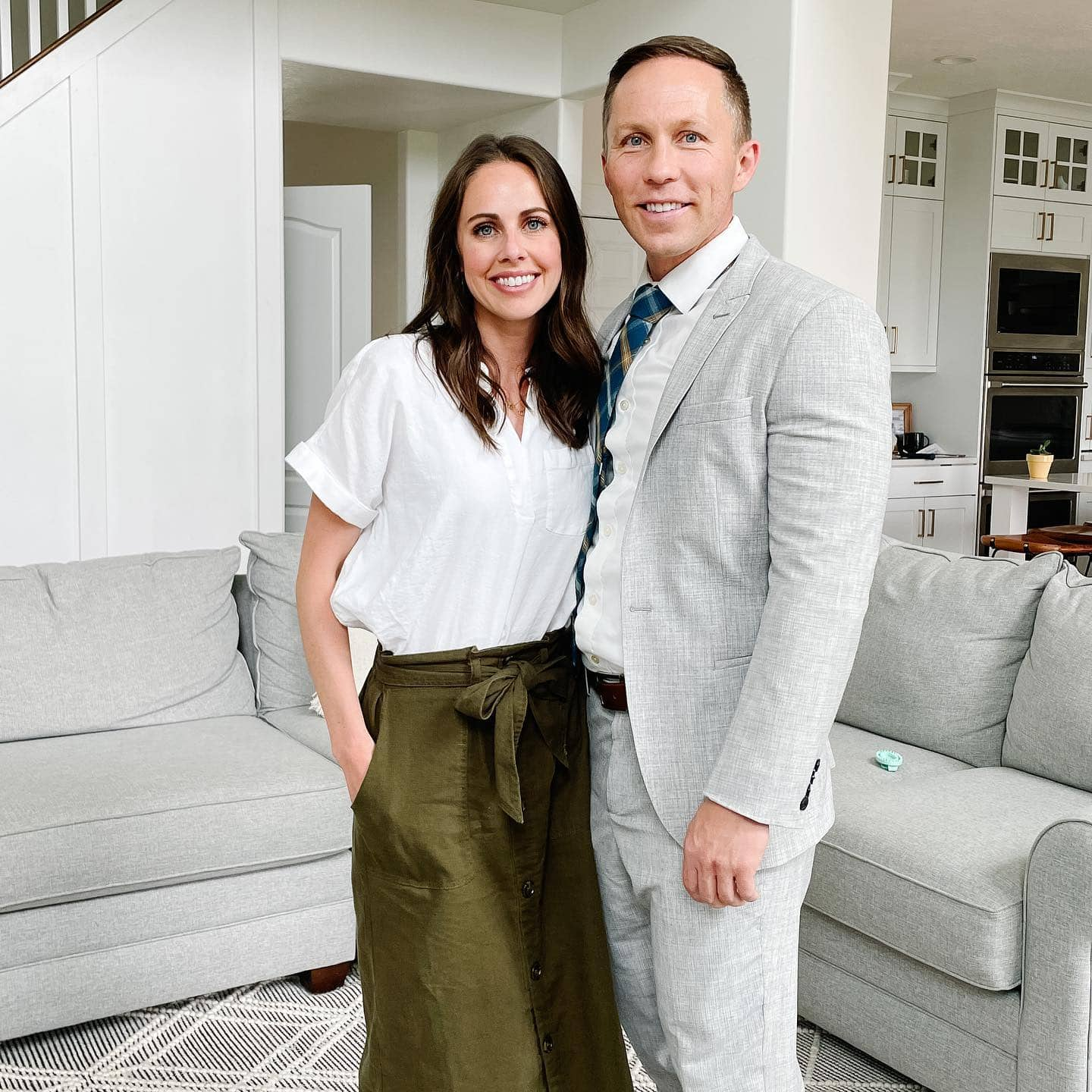 a photo of a husband and wife standing in front of a gray couch in Sunday dress.