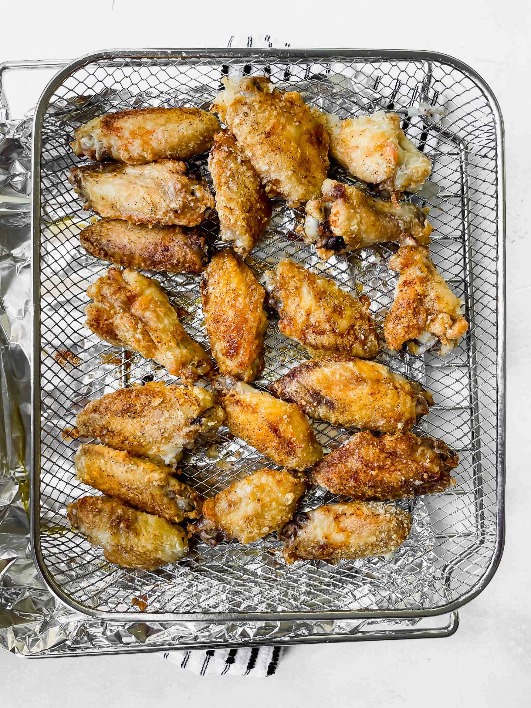 a photo of a metal cooling rack topped with several crispy chicken wings.