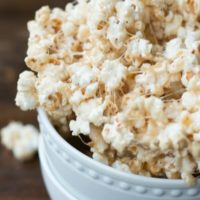 Easy and delicious marshmallow popcorn recipe in two small white bowls on top of a wooden table.