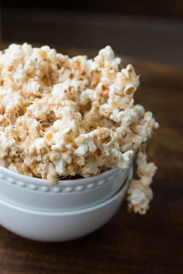 Delicious Marshmallow Popcorn in two white bowls on a wooden table.