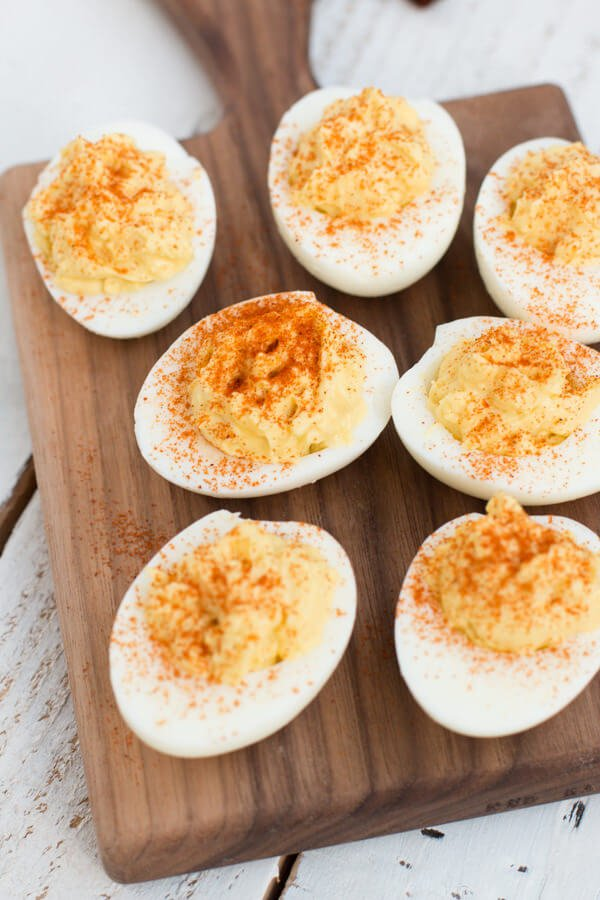 Seven of the best Deviled Eggs on a wooden platter on top of a white wooden table.