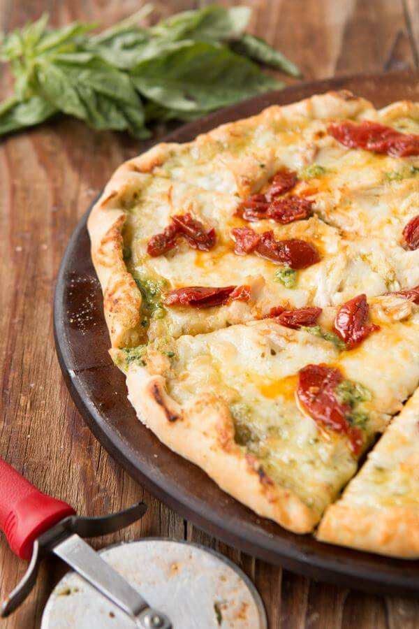 Creamy Pesto Chicken and Sun Dried Tomatoes has this really chewy and delicious thin crust and is definitely one of my favorites! ohsweetbasil.com