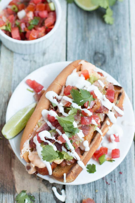 Sonoran hot dogs are like the ultimate hot dog. Loaded with beans, cheese sauce, bacon, pico de gallo, guacamole, and sour cream! ohsweetbasil.com-8