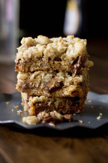 You will fall in love with these #Reeses Crumble bars. Buttery oatmeal cumble stuffed with chocolate chips and #Reesespeanutbuttercups ohsweetbasil.com_