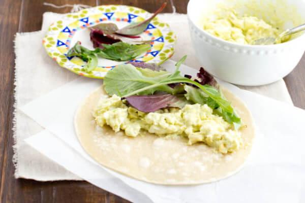 Avocado Egg Salad Wrap next ti a white bowl egg salad on white napkins.