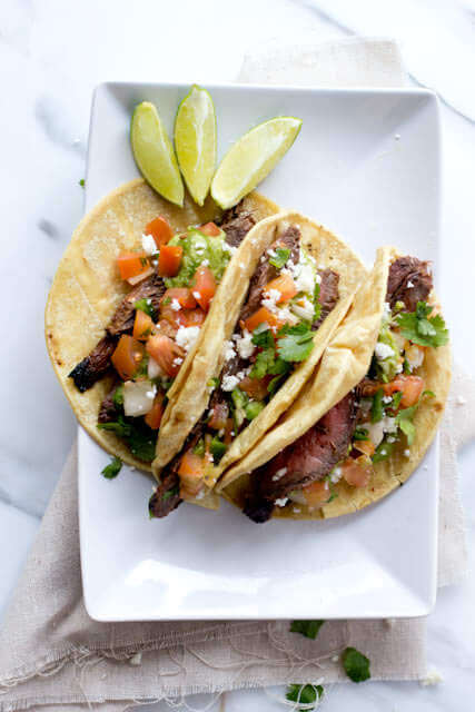 Three easy authentic carne asada tacos in corn tortillas with three slices of lemon on a white serving plate.