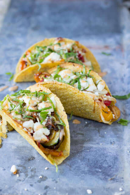 Vegetarian tacos with spicy crema. Fresh veggies sauteed and stuffed into a crunchy delicious taco topped with creamy queso fresco ohsweetbasil.com