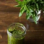 Classic Pesto Recipe in a clear jar on a wooden table.