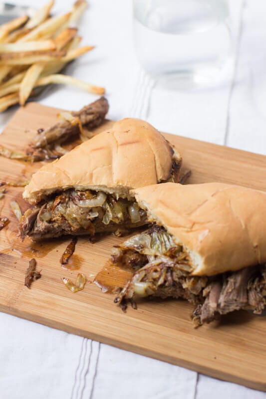 Easy Pot Roast sandwich cut in half on a wooden board on top of a white table cloth.
