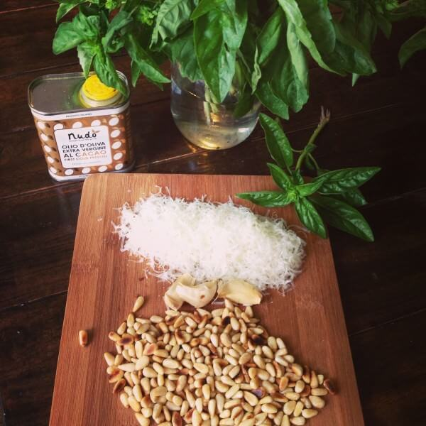 Wooden cutting board with pine nuts, parmesan cheese, garlic, basil, olive oil and a pinch of salt.