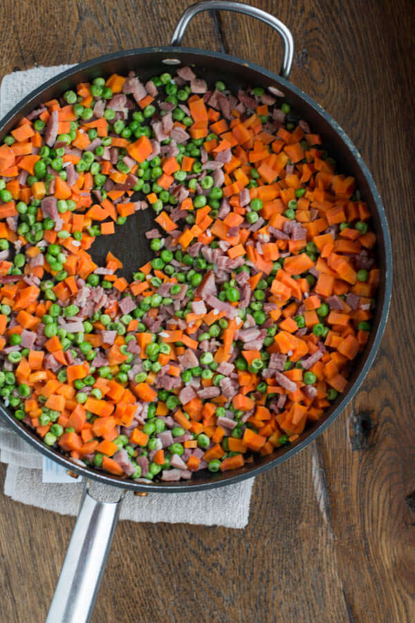 Ham, peas and carrots in a pan on a wooden table.