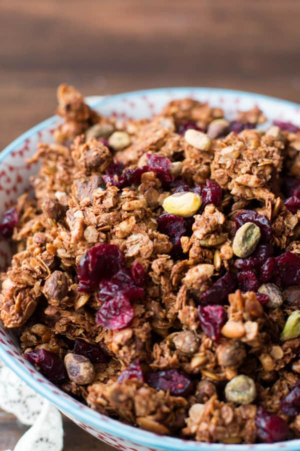 Our new favorite granola! Pistachio pomegranate granola is so easy to make and I've been loving it as a mid day snack! ohsweetbasil.com pepitas, oats, maple syrup