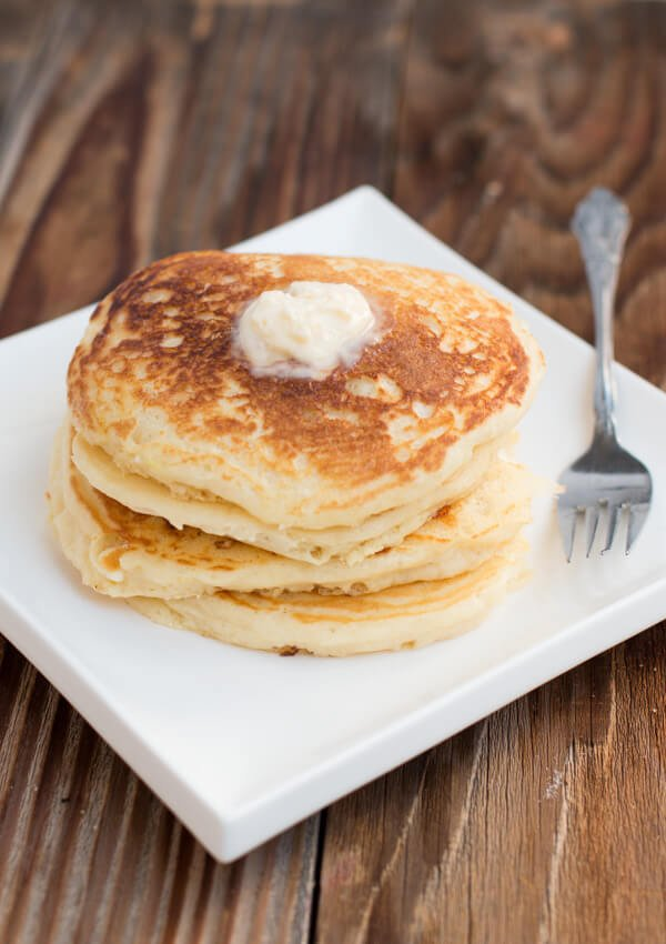 stack of fluffy buttermilk pancakes on white plate