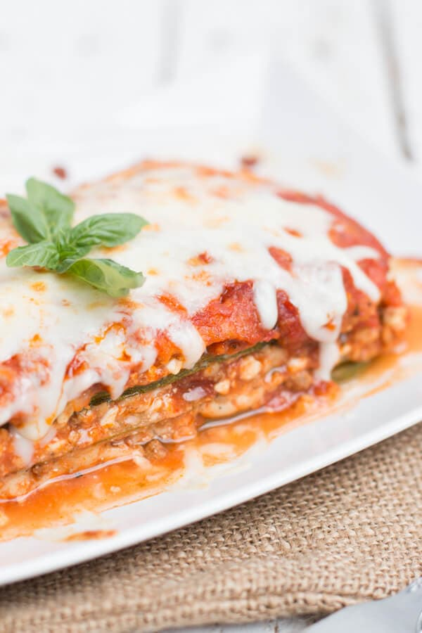 side view of low carb zucchini lasagna on white plate