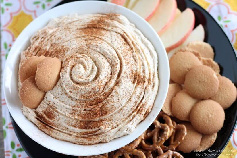 pumpkin cream cheese Dip surrounded by pretzels, wafers and sliced red apples on a black plate.