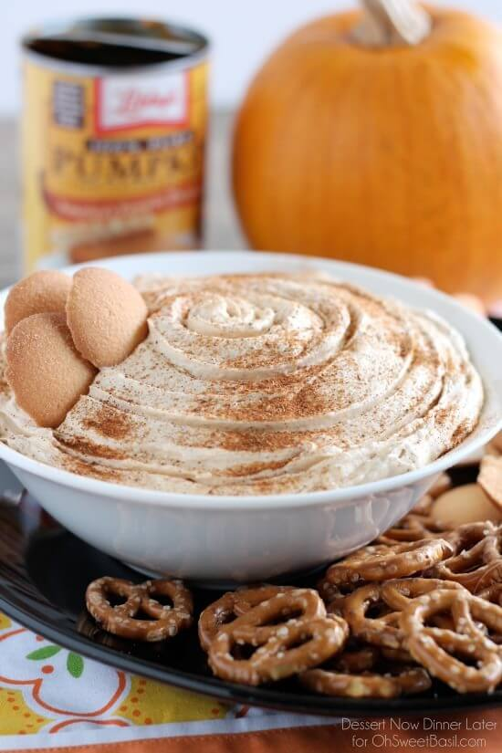 Pumpkin Cheesecake Dip in a white bowl with pretzels on the side and a pumpkin in the background.