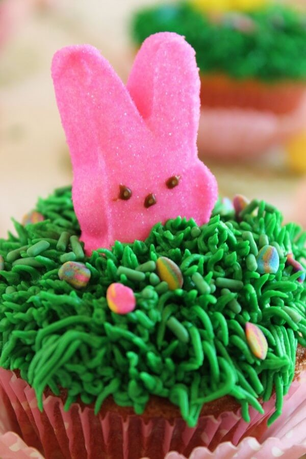 "Say ""Hello"" to spring with these festive Cadbury Mini Egg Cupcakes! Decorated with a cute bunny peeking out of the grass, these easy to make cupcakes are the perfect Easter treat."