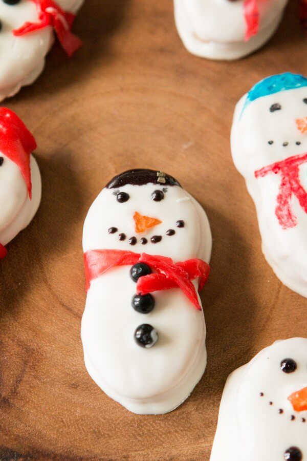 These Nutter Butter Snowmen will bring a smile to your face on a cold winter day! Dipped in white chocolate and topped with fruit roll ups, they are a festive, delicious, ADORABLE treat just in time for the class Christmas party! Christmas cookies, no-bake dessert, 5 minutes