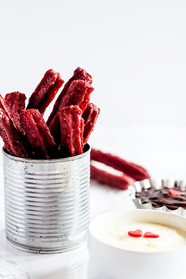A aluminum cup full of Red Velvet Churros with a nutella and cream cheese dip