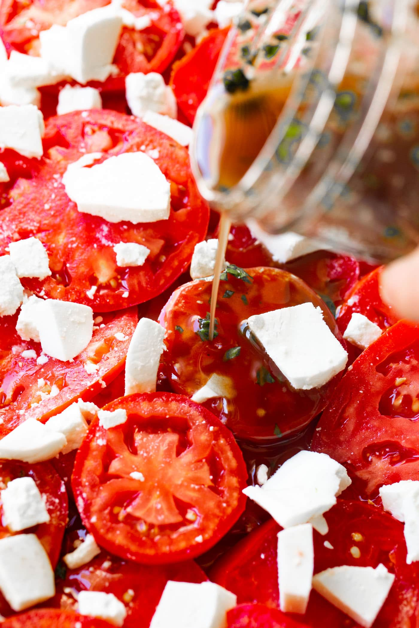 A photo of balsamic vinegar dressing being poured over marinated tomatoes salad.
