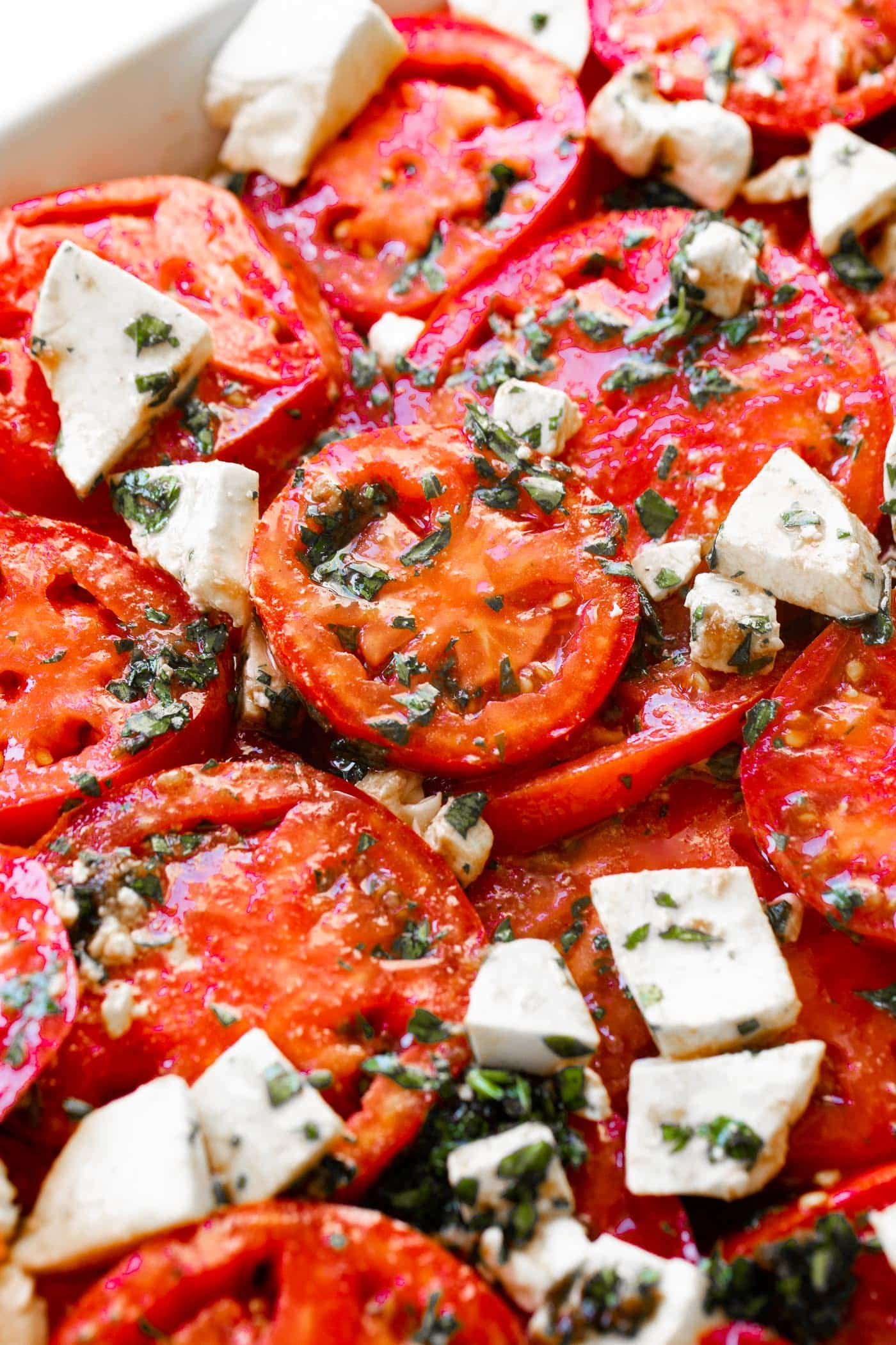 A photo of a marinated tomatoes salad with fresh herbs and 3 cheeses.