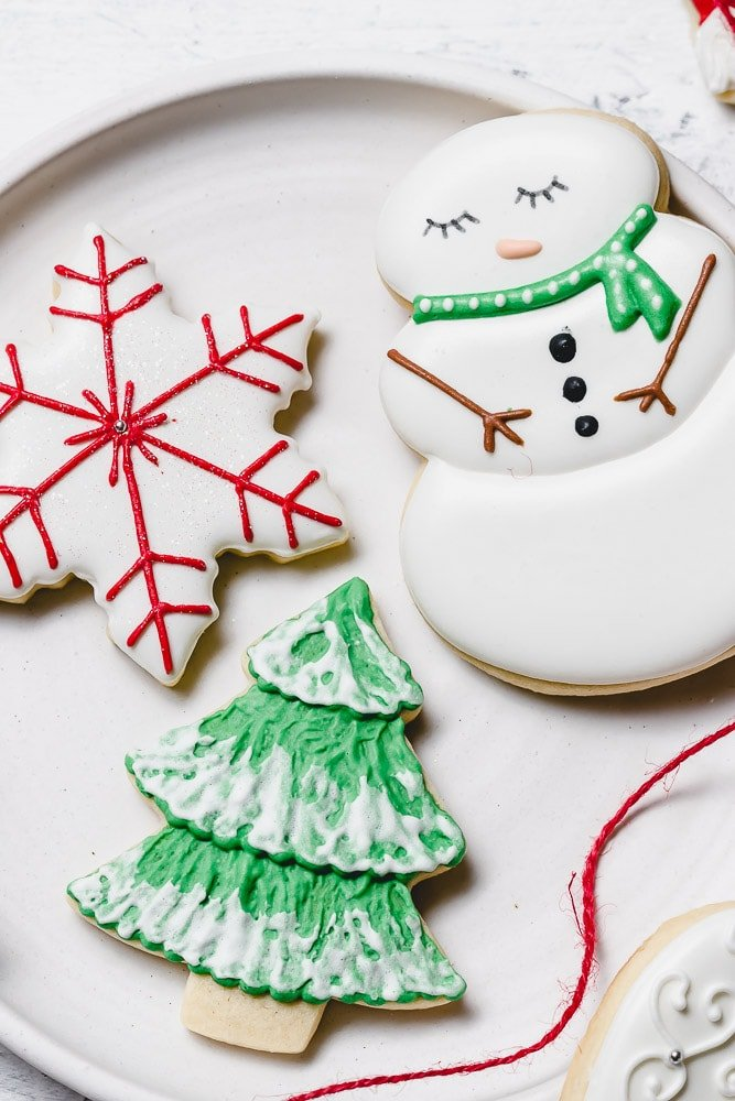 Christmas Sugar cookies with royal icing. There is a snowman with a green scarf, a tree with green icing and white accents like snow, and a white star with red designs.