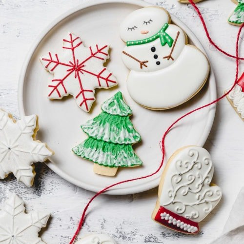 A plate with Christmas sugar cookies decorated with royal icing. There is a snowman with a green scarf, a white mitten with red trim, a green tree with white snow accents, and a white star with red accents. A red ribbon is draped over the edge of the plate.