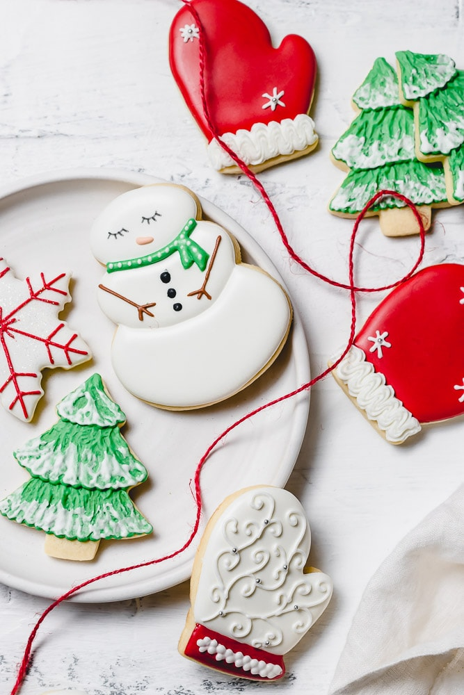 Christmas sugar cookies decorated with royal icing. There is a snowman with a green scarf, a red mitten, a snowflake with red accents, a green tree with white snow.