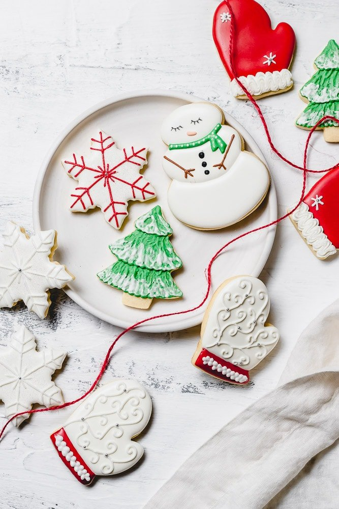 A plate of Christmas sugar cookies decorated with royal icing. There is a snowman with green scarf, a snowflake with red accents, a green tree with white snow, a white mitten with red trim, and white snowflakes