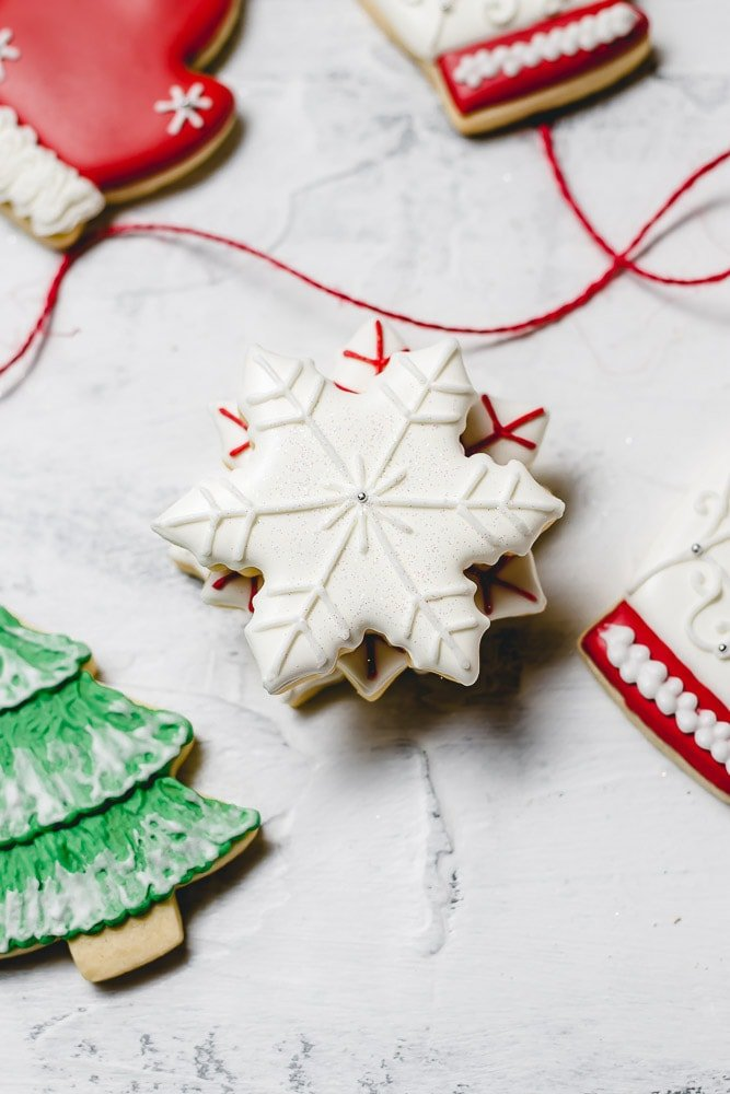Christmas sugar cookies decorated with royal icing. There is a thin red ribbon on the table next to a white snowflake cookie with white accents, a white mitten with red trim and a green tree with white snow accents.