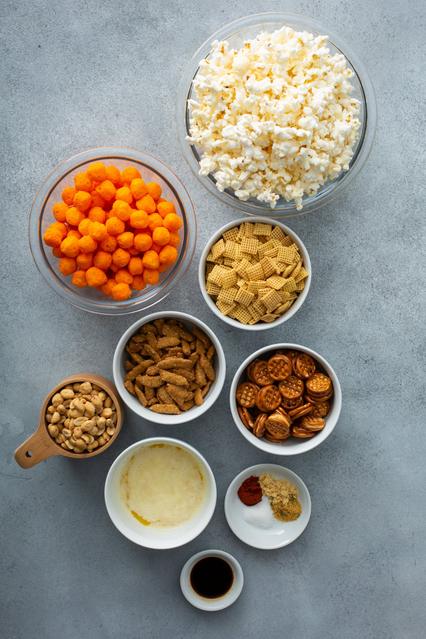 Containers of ingredients for a savory snack mix. There is popcorn, cheese balls, pretzels, sesame sticks, peanuts and spices.