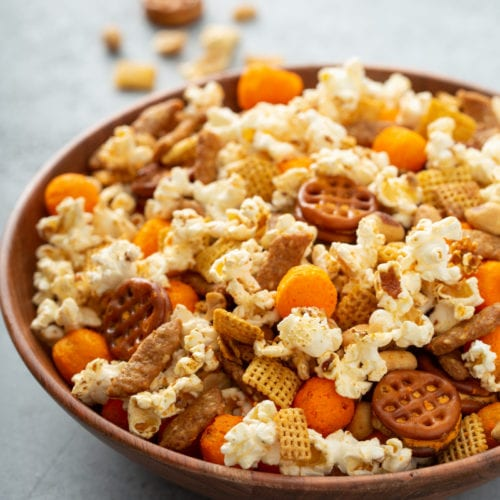 A bowl of 5 minute March madness snack mix. It has popcorn, cheese balls, pretzels, peanuts, and sesame sticks.