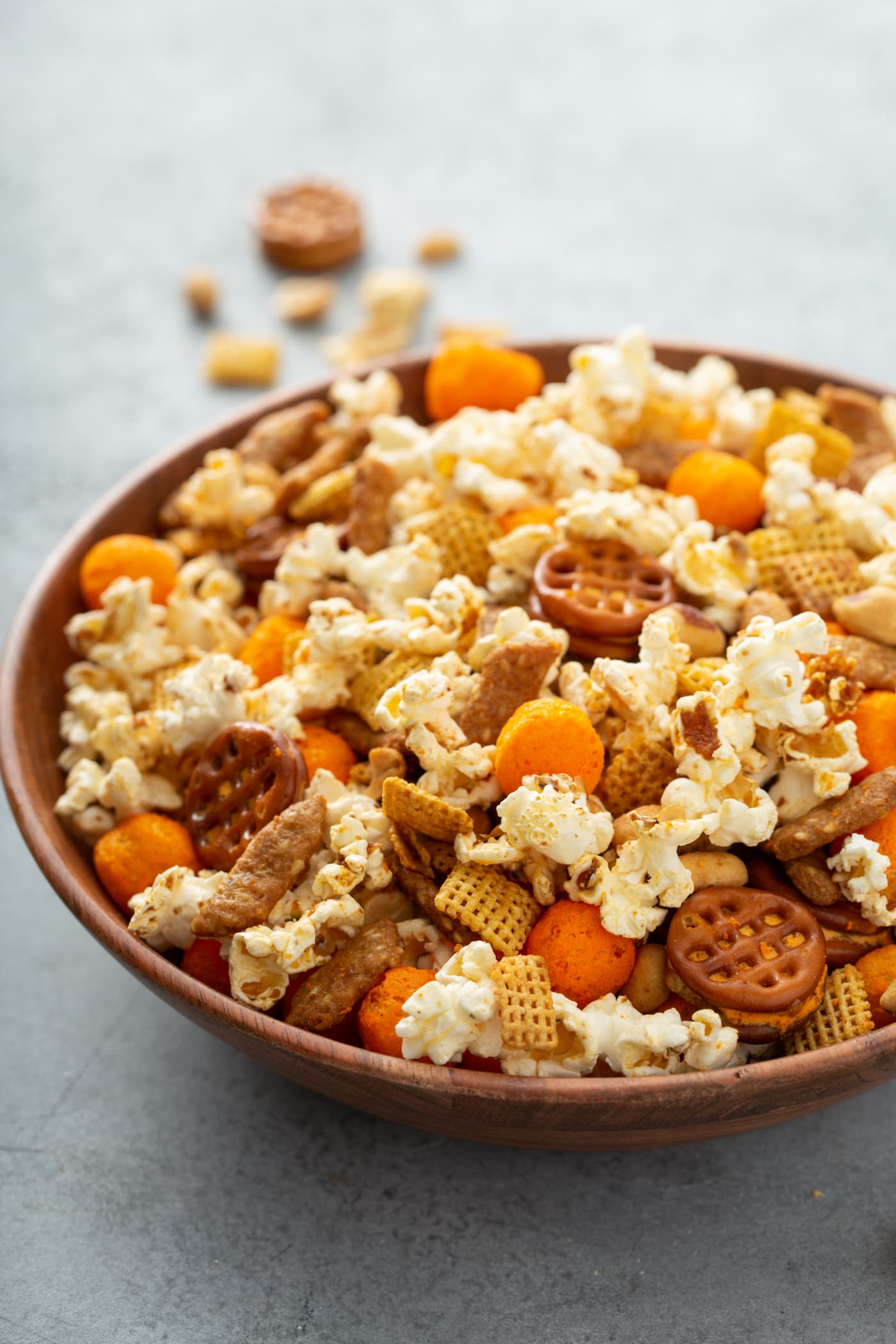 A bowl of March madness snack mix. It has popcorn, cheese balls, pretzels, peanuts, and sesame sticks.