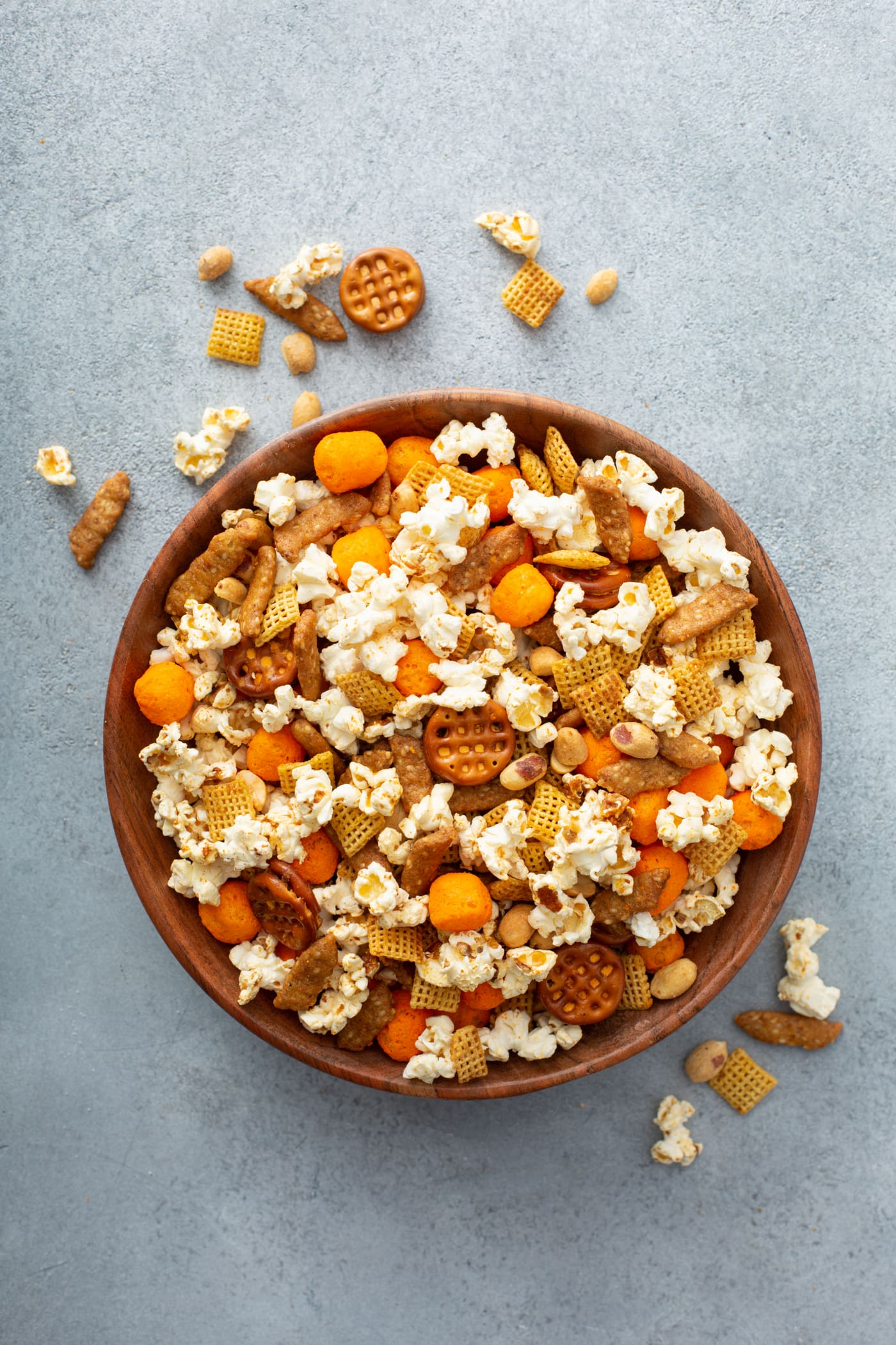A bowl of March Madness snack mix. It contains popcorn, peanuts, cheese balls, pretzels, chex and sesame sticks.