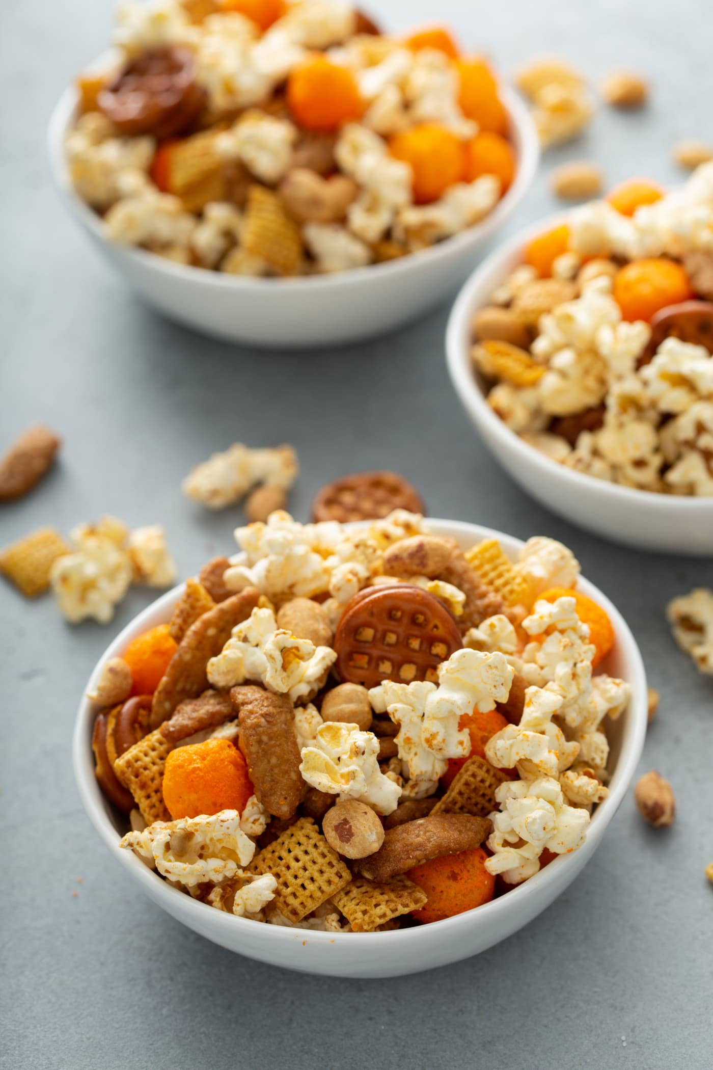Three bowls of March madness snack mix. It contains popcorn, peanuts, chex, pretzels and sesame sticks.
